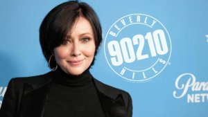 Shannen Doherty posing in front of a 90210 backdrop