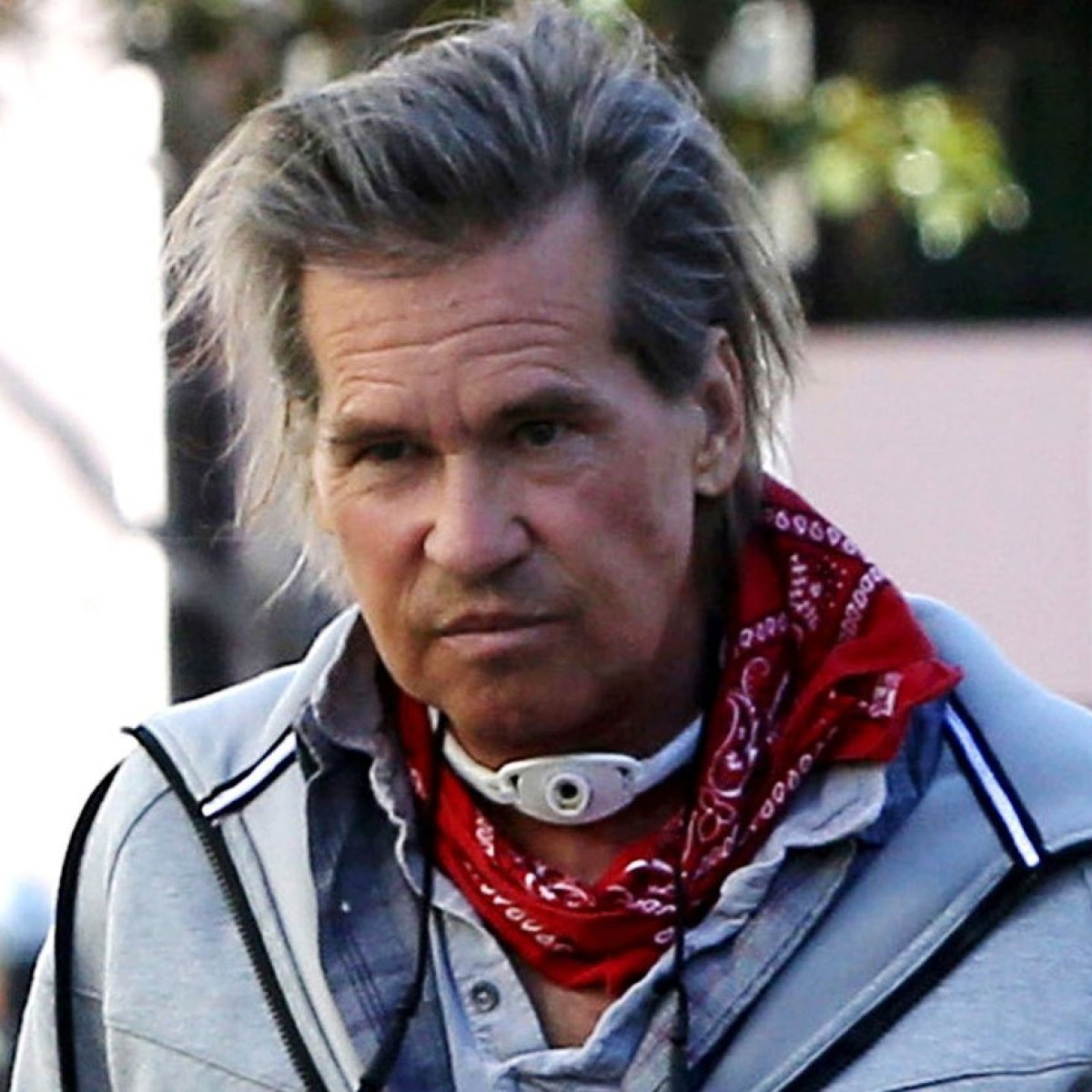Val Kilmer wearing trachea breathing device and covers it up with red bandana