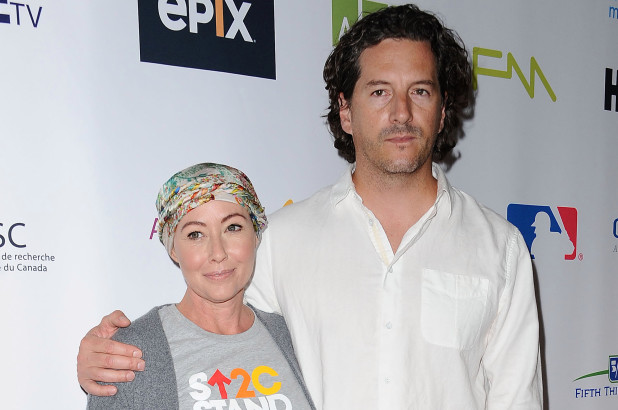 Shannen Doherty and her husband. Doherty is wearing a stand up to cancer t shirt and a head wrap and her husband is wearing a white button down