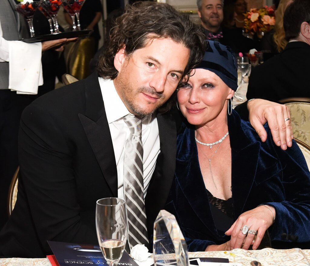 Shannen Doherty and her husband in 2016 as she was undergoing cancer treatment. This is at a ceremony and she is wearing a blue outfit with a blue head wrap