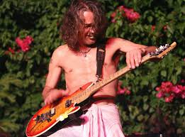 Eddie Van Halen rocking out on his guitar with a metal guitar pick in his mouth