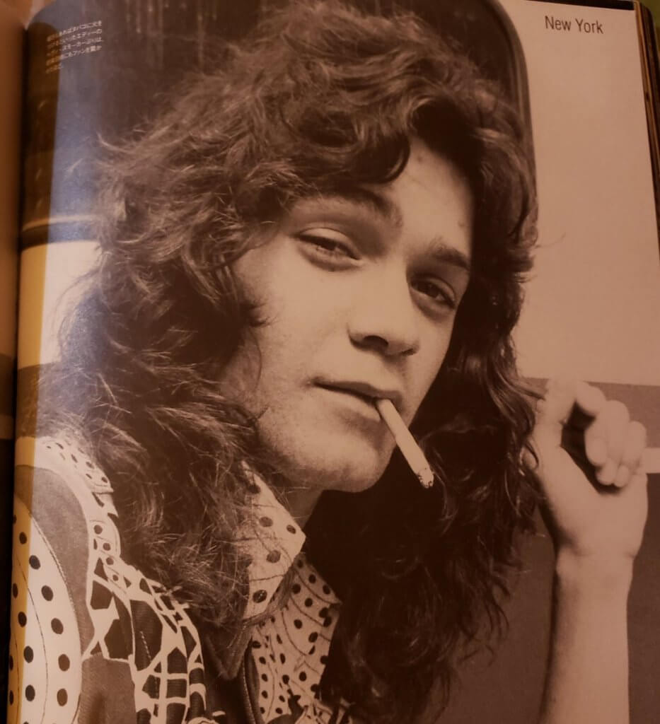Eddie Van Halen smoking a cigarette in the early days with his long, curly hair