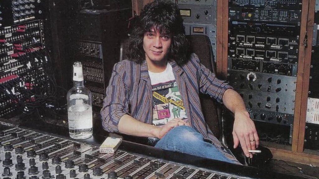 Eddie Van Halen with long hair in a music studio with a bottle of alcohol next to him
