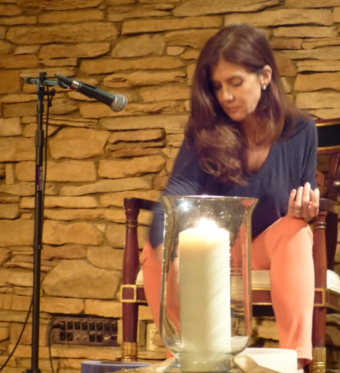 Jean Trebek sitting in a wooden chair in front of a microphone with a candle in front of her leading one of her Religious Science practices