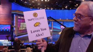 "Kirk Hessler, who attended the ""Jeopardy!"" taping with the Taft College crew, holds up a sign for Alex Trebek reading ""Taft College Loves You Alex!"""