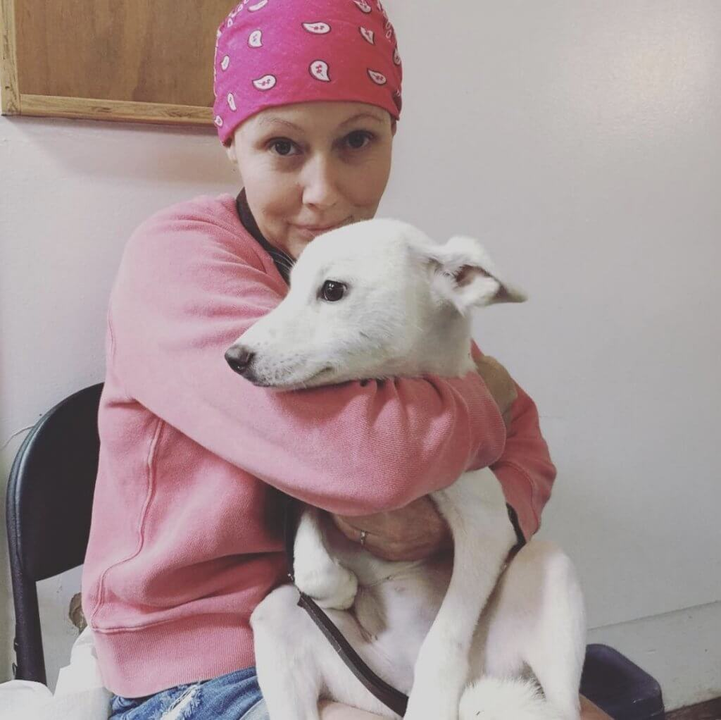 Shannen Doherty with a pink bandana covering her head hugging a dog
