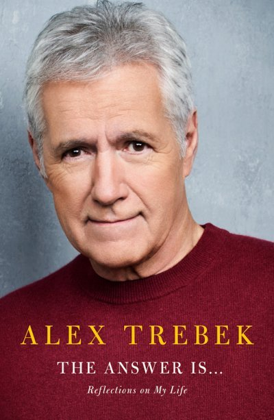 The cover of Alex Trebek's 'The Answer Is . . .: Reflections on My Life' Book, a picture of him with a red sweater and a gray wall background