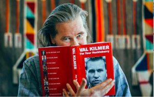 Val Kilmer posing with his bestselling book