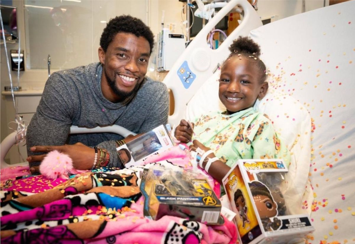 Chadwick Boseman at cancer hospital with child